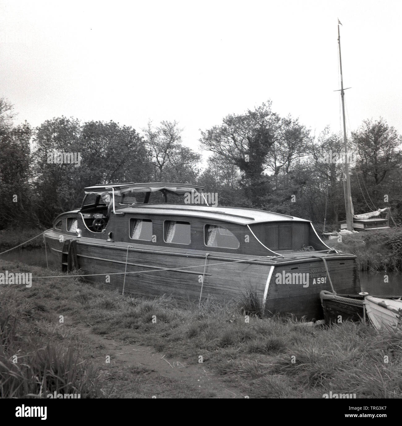 1950s, historical, a man on a wooden cabin cruiser boat