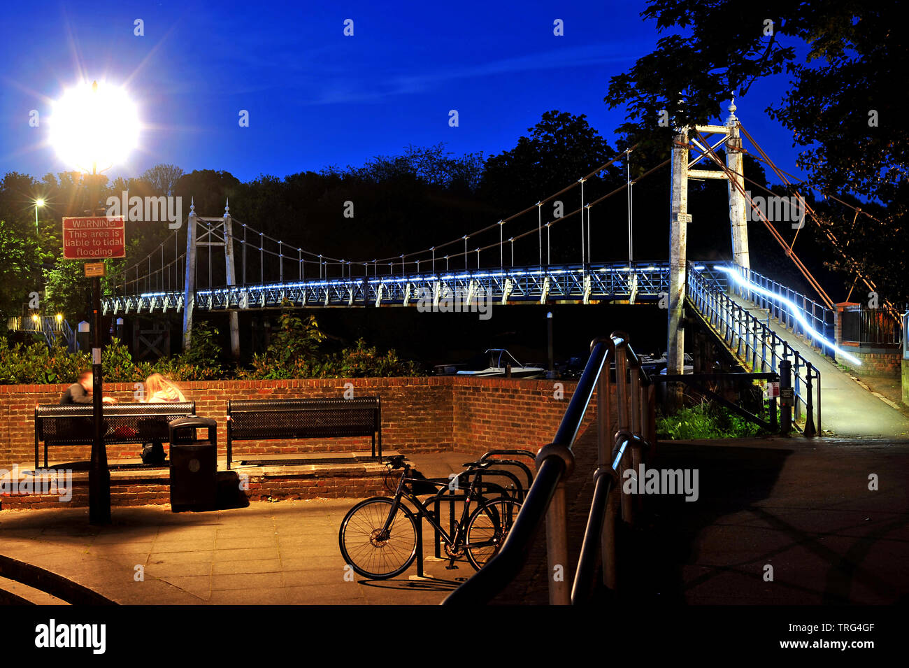 The suspension bridge over Teddington Lock allowing pedestrians to cross the river Thames from Ham to Teddington, Middlesex. Photographed at night - Stock Image