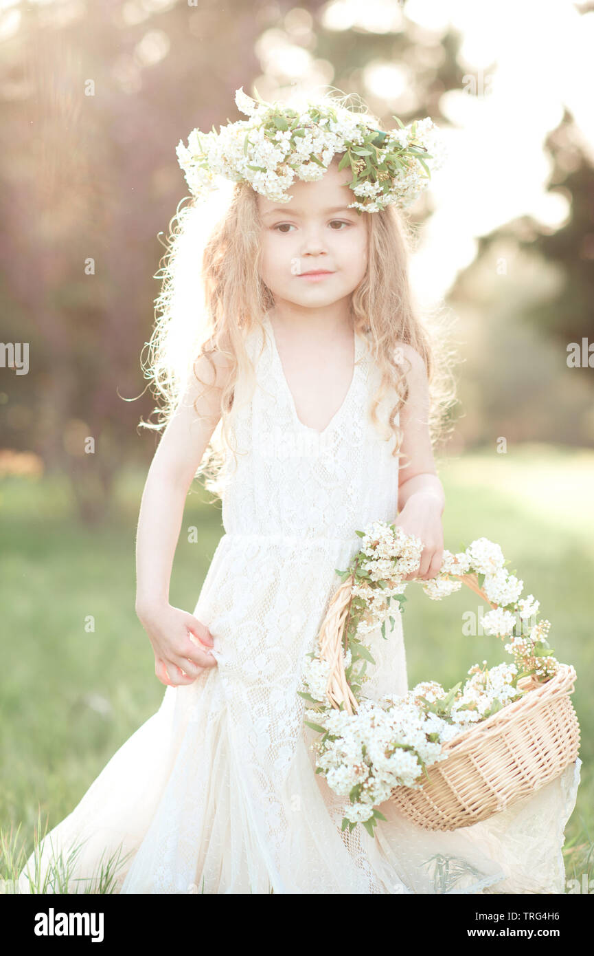0cdcf40f33 Cute baby girl 3-4 year old wearing trendy white dress and floral wreath  outdoors. Holding basket with flowers. Childhood. Wedding day.