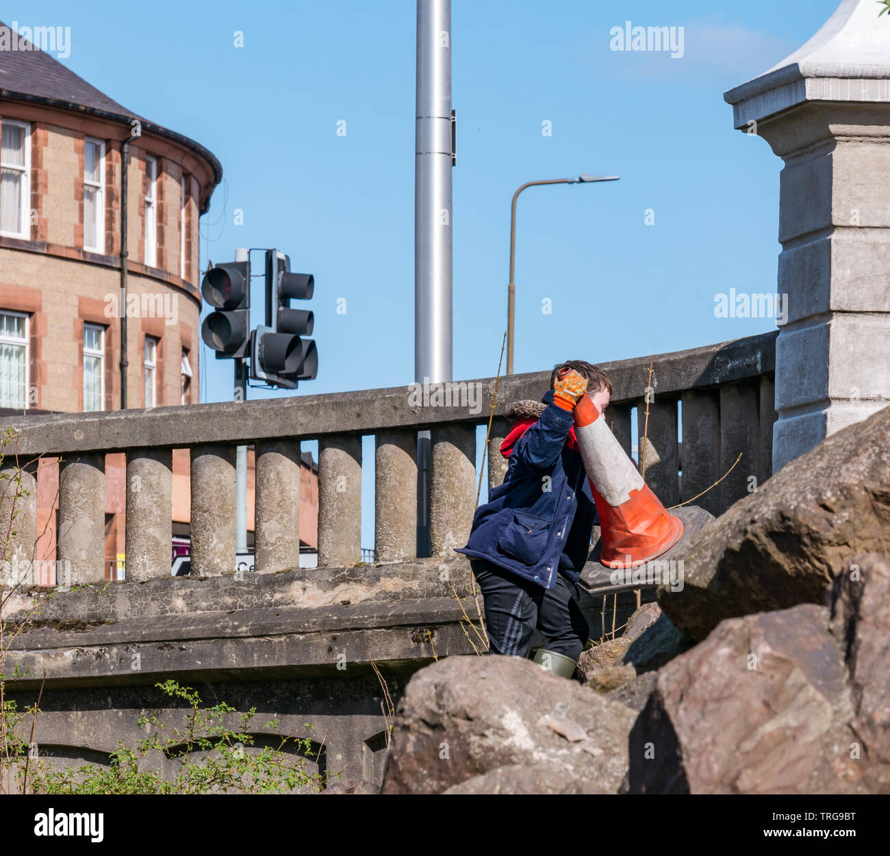 Volunteer at annual Spring clean on bank of Water of Leith, Edinburgh, Scotland, UK. A young boy retrieves a traffic cone from the riverbank - Stock Image
