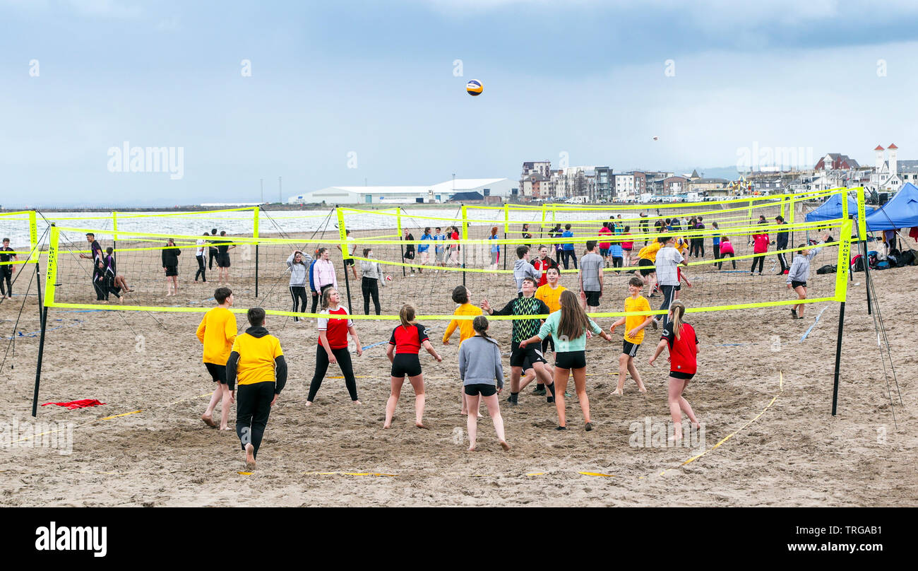 Ayr, UK, Scottish Volleyball Association organised the first school's beach volleyball competition held in Scotland, where 180 secondary school children, aged over 13 years, forming 40 teams from across the West of Scotland were invited to take part. The competition, won by  St Matthews Academy, Saltcoats (wearing yellow) was overseen by the members Scottish Volleyball Association who were hoping to identify potential future international team players and put them on a pathway to success. Credit: Findlay/Alamy Live News - Stock Image