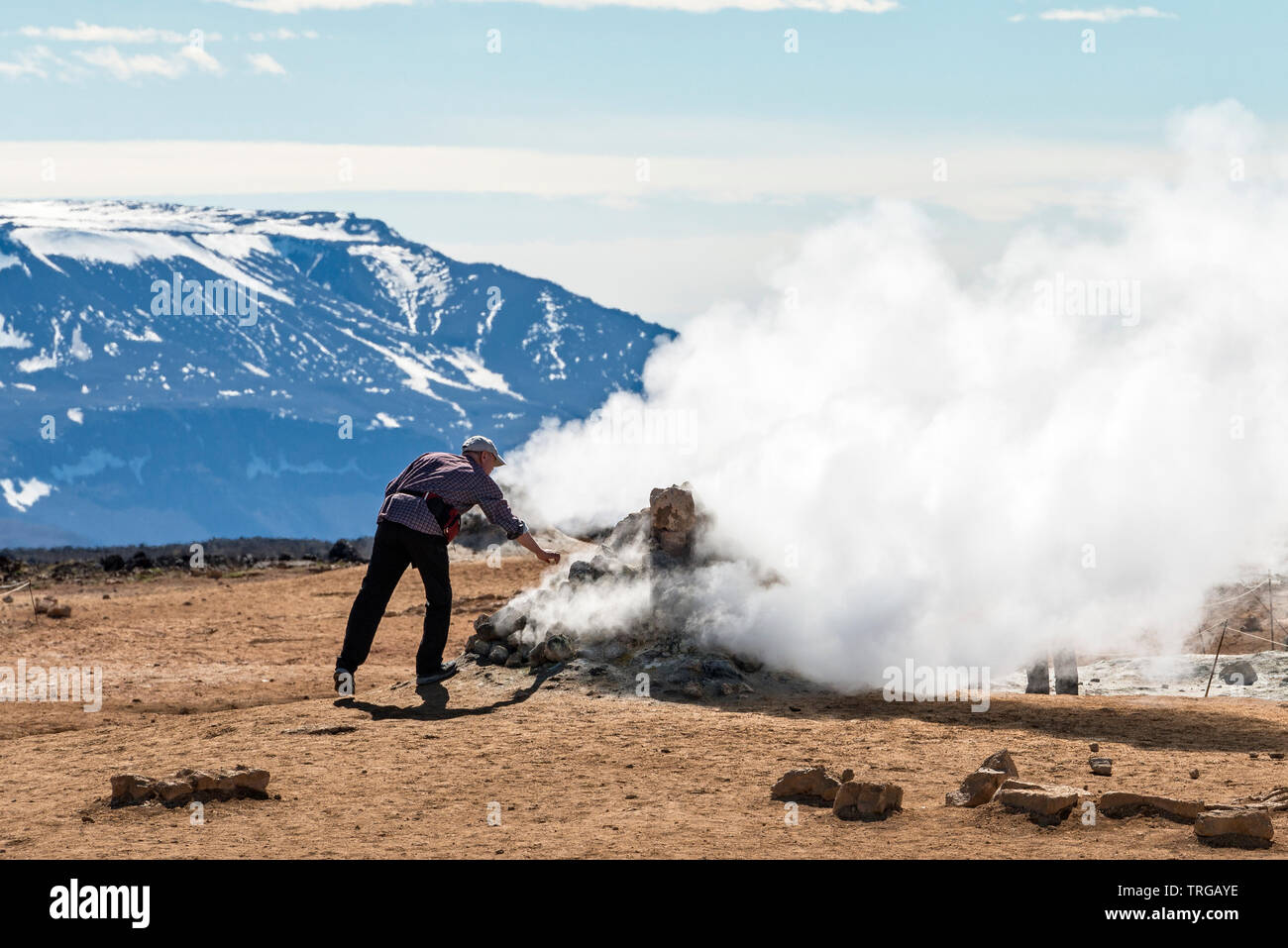 A tourist unwisely tests the heat of a fumarole in the highly active geothermal area at Námafjall (Hverir), near Lake Mývatn in north-east Iceland - Stock Image