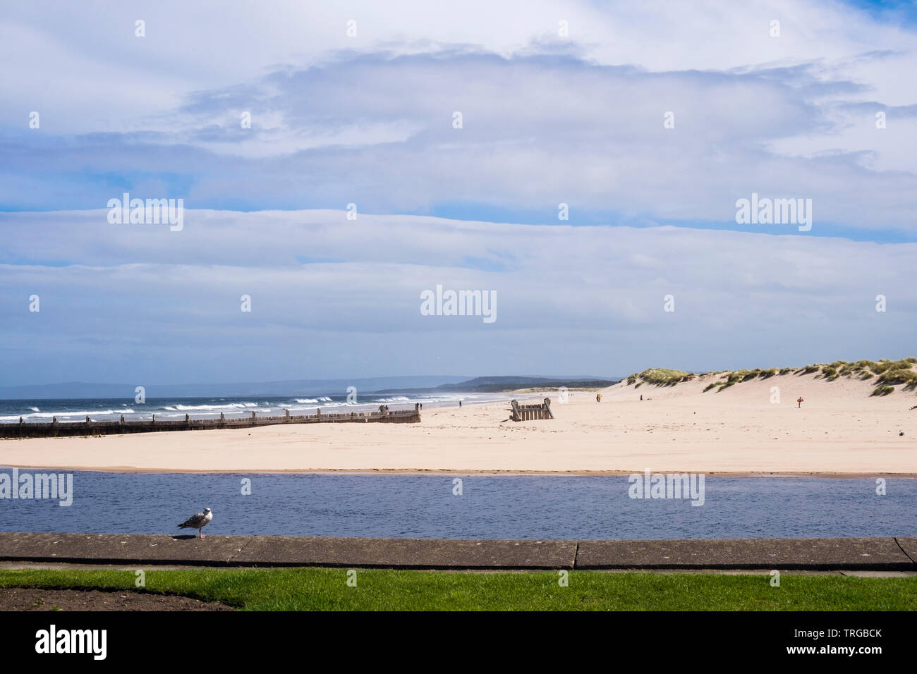 View to east beach and sand dunes across Lossie River mouth from waterfront promenade on Moray Firth coast. Lossiemouth, Moray, Scotland, UK, Britain Stock Photo
