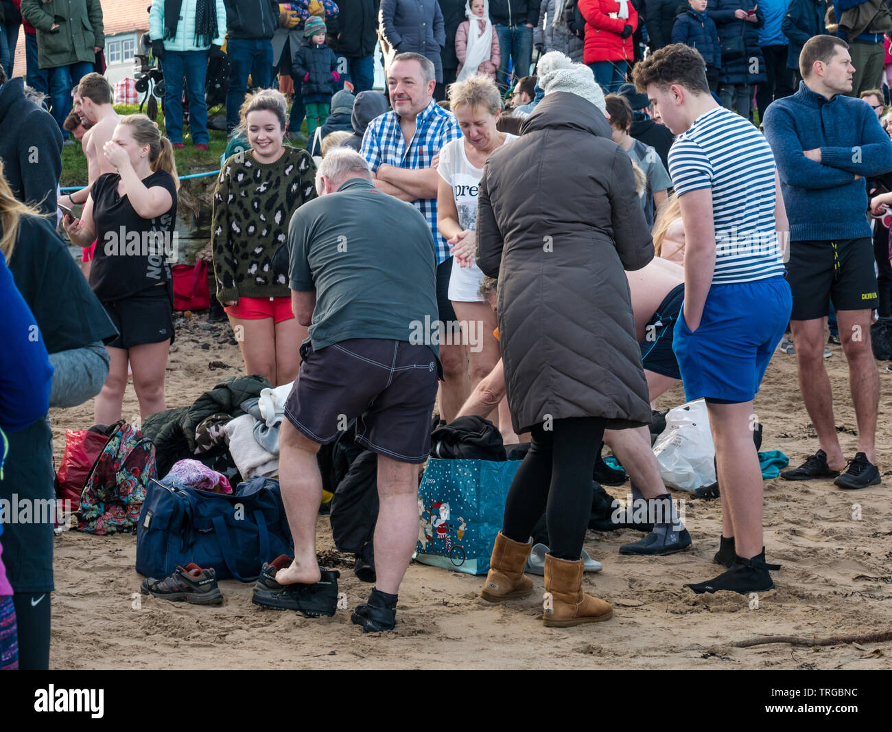 Loony Dook, New Year's Day: People brave the cold water of West Bay, Firth of Forth, North Berwick, East Lothian, Scotland, UK. People getting changed - Stock Image
