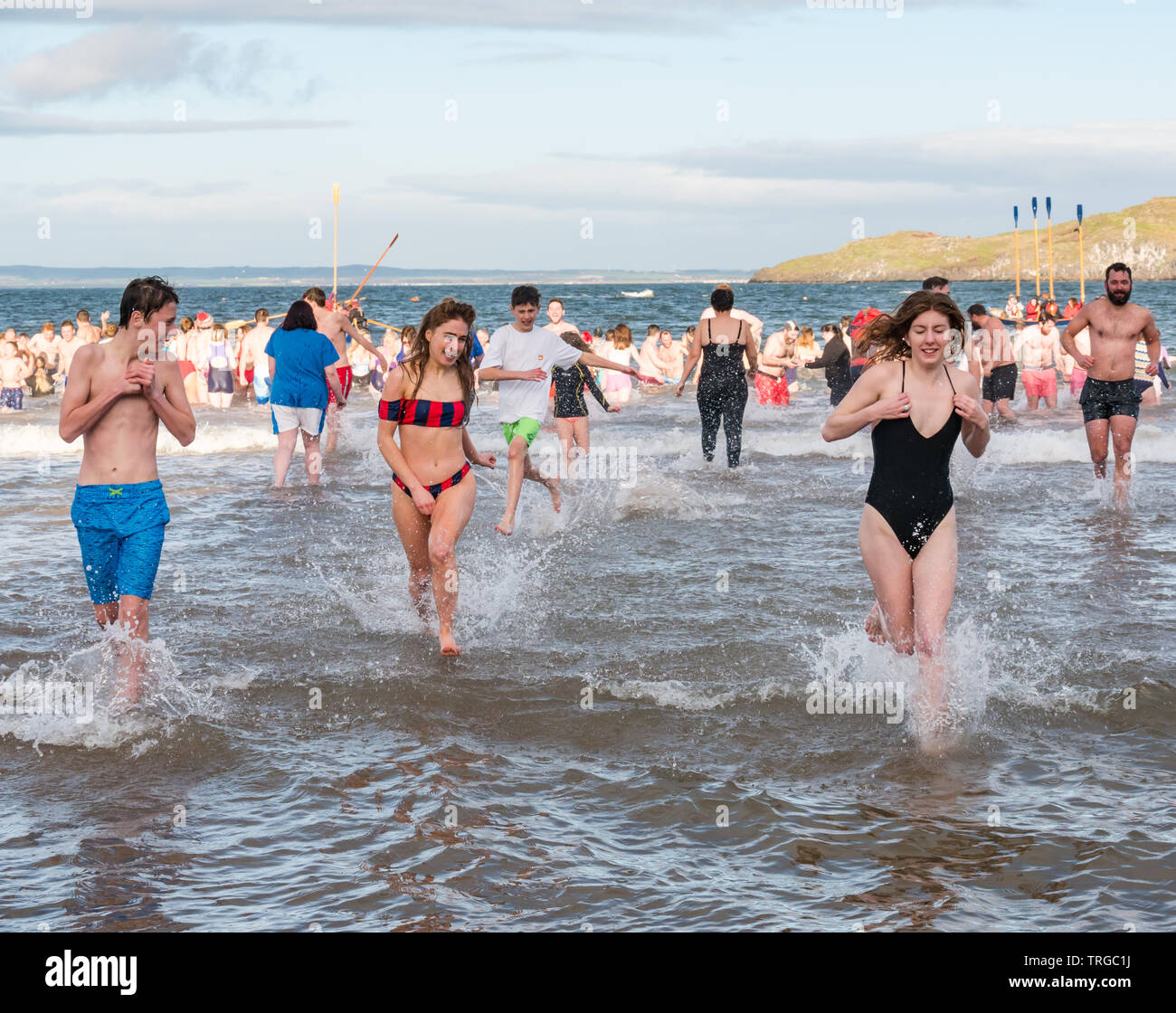 Loony Dook , New Year's Day: People brave the cold water, West Bay, Firth of Forth, North Berwick, East Lothian, Scotland, UK. People run into the sea - Stock Image