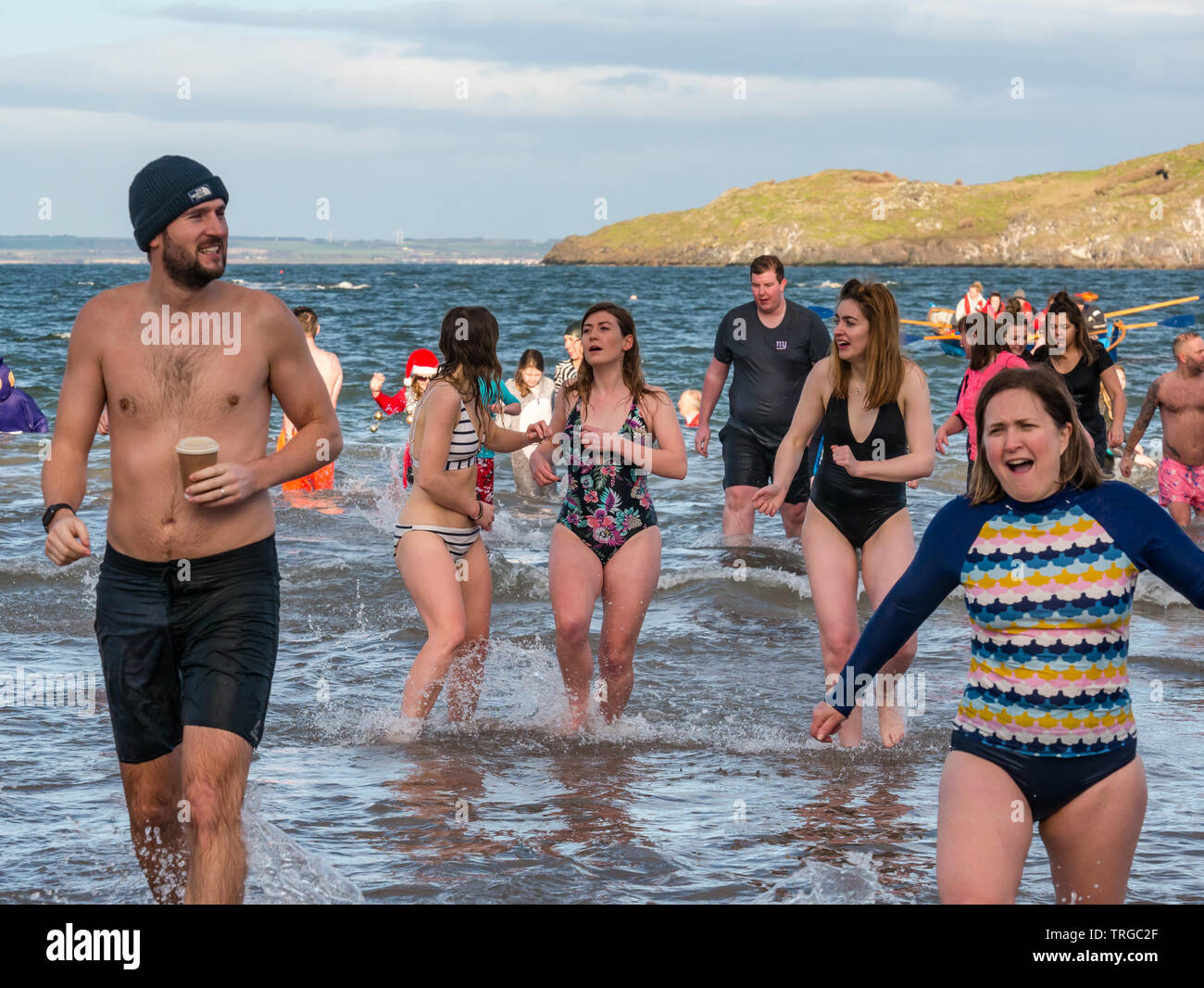Loony Dook , New Year's Day: People brave cold water, Firth of Forth, North Berwick, East Lothian, Scotland, UK. Young women in swimsuits looking cold - Stock Image