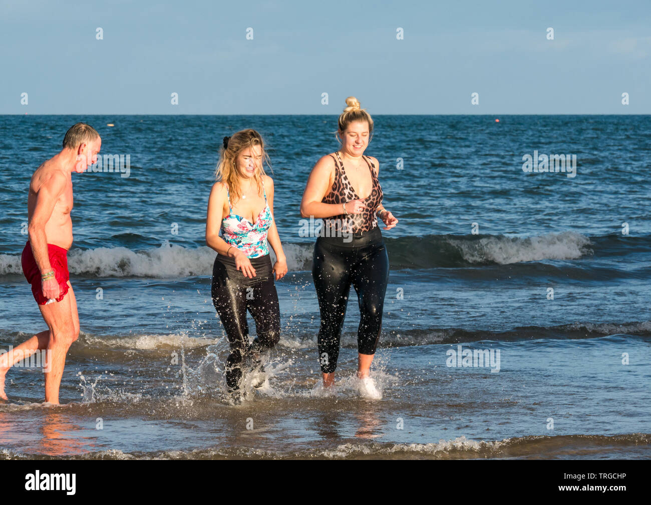 Loony Dook, New Year's Day: People brave cold water, West Bay, Firth of Forth, North Berwick, East Lothian, Scotland, UK. Young women come out of sea - Stock Image