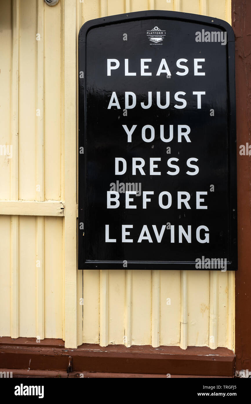 Please adjust your dress sign, Dartmouth, Devon, UK - Stock Image
