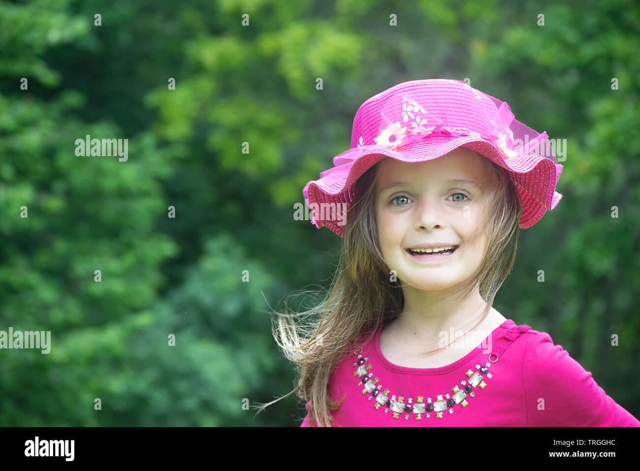 Outdoor portrait of a little girl wearing a summer hat. Copy space to the left. - Stock Image