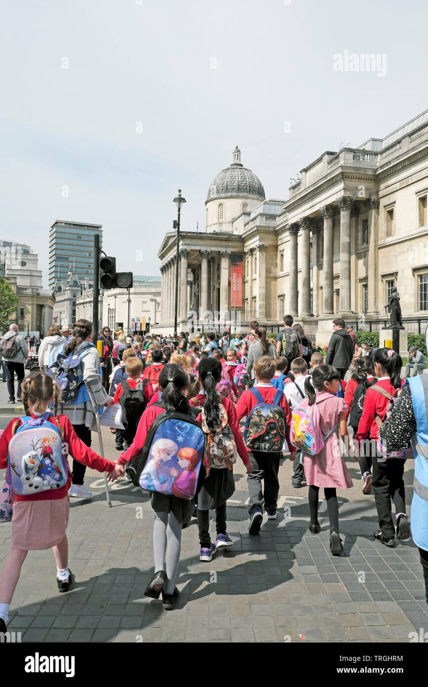 Group of primary school students pupils and teacher walking along the street to visit  the National Gallery London England UK  KATHY DEWITT - Stock Image