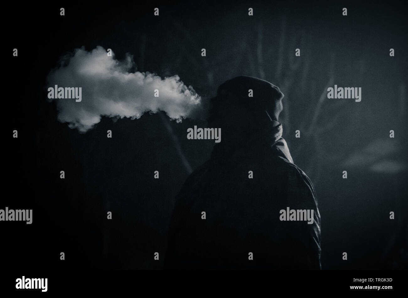 strange man smoking at night with big steam effect from the cigarette - Stock Image