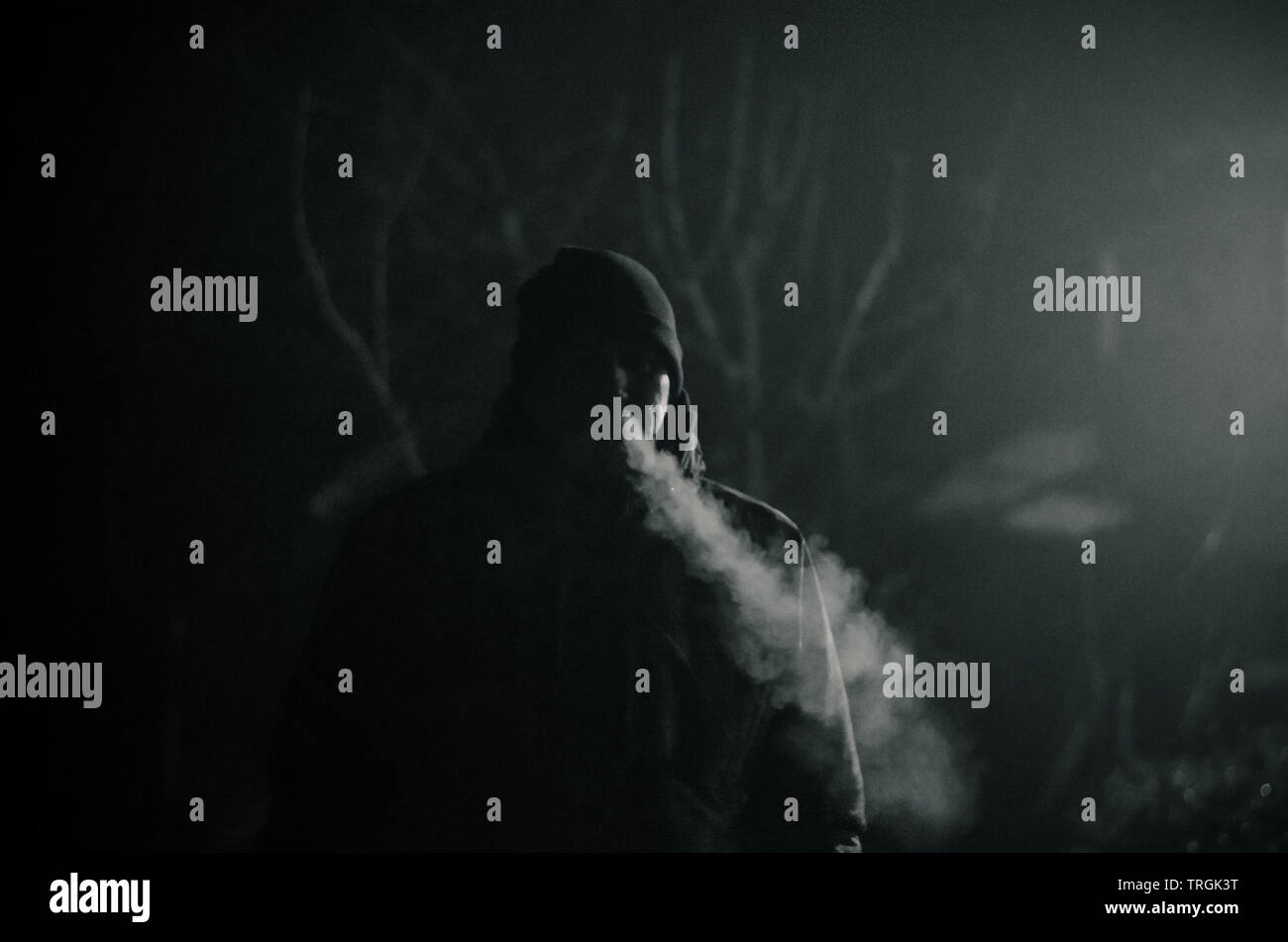 man silhouette smoking like chimney at night with backlight - Stock Image