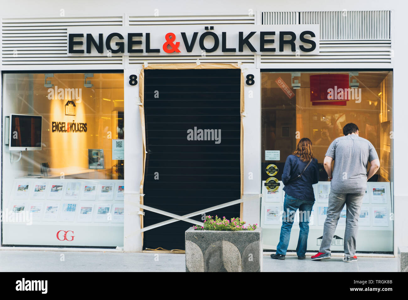 Valencia, Spain - June 1, 2019:: A couple looking at showcase of Engel and Volkers real estate agency in Valencia. View from behind. - Stock Image