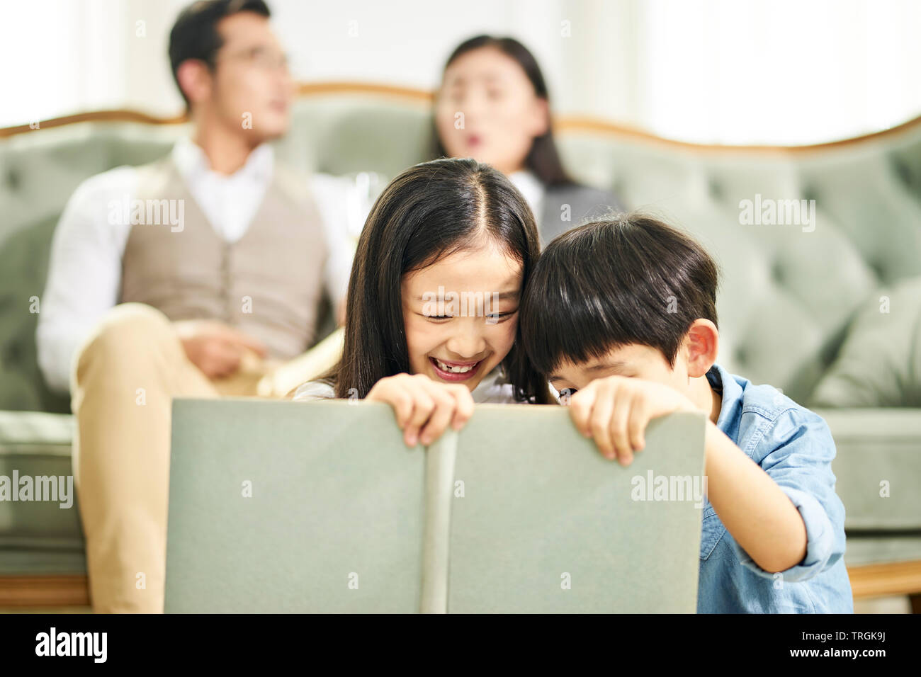 two asian kids brother and sister sitting on carpet reading book together in family living room with parents sitting on couch in the background. Stock Photo