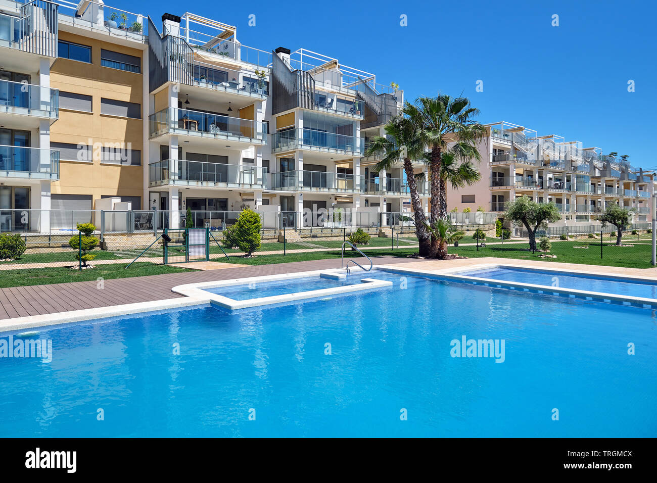 Torrevieja, Spain - April 24, 2019: High rise residential multi-storey house closed urbanization with swimming pool, waterside view, no people. Provin - Stock Image