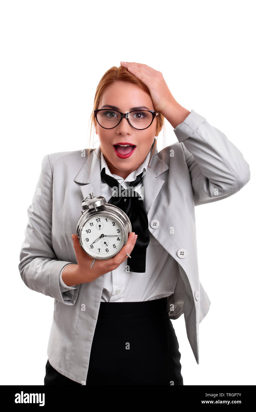 Beautiful young business woman dressed in a suit holding a clock with shocked expression, isolated on a white background. - Stock Image