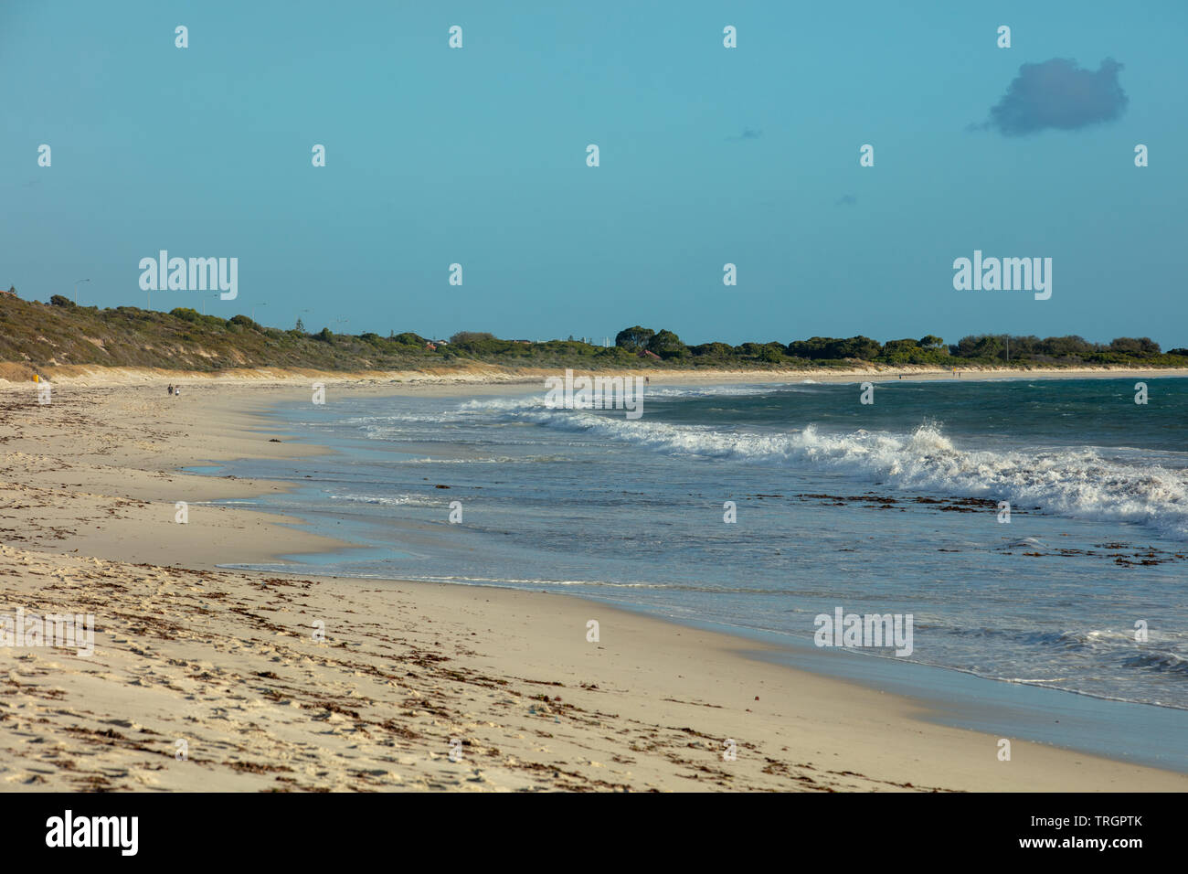 Part of Mullaloo beach in western Australia on a sunny but breezy autumn day in April with some people walking on the sand in the far distance. - Stock Image