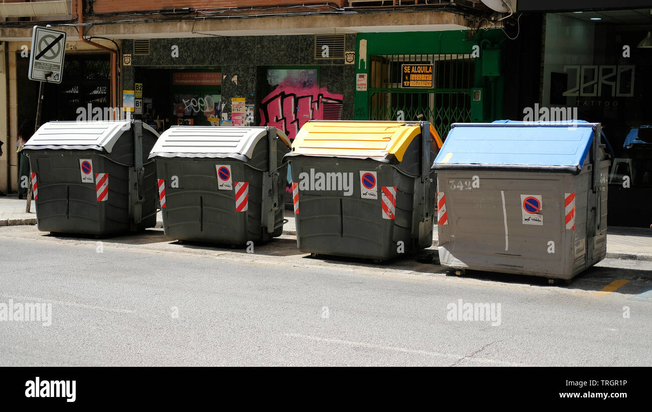 Recycling bins for different recyclables on a street in Granada, Spain. - Stock Image