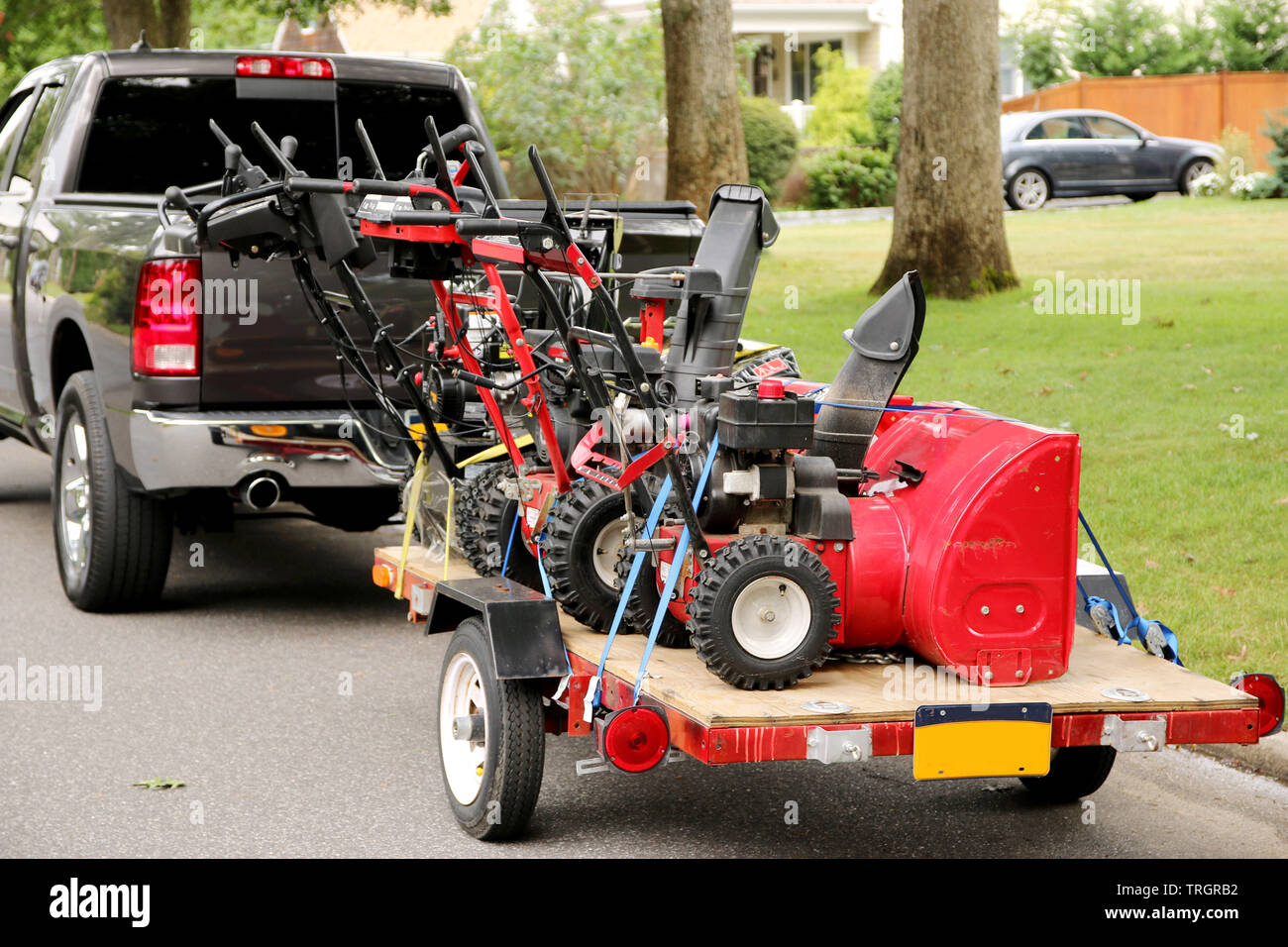 Three snowblowers on a trailer being towed by a truck - Stock Image