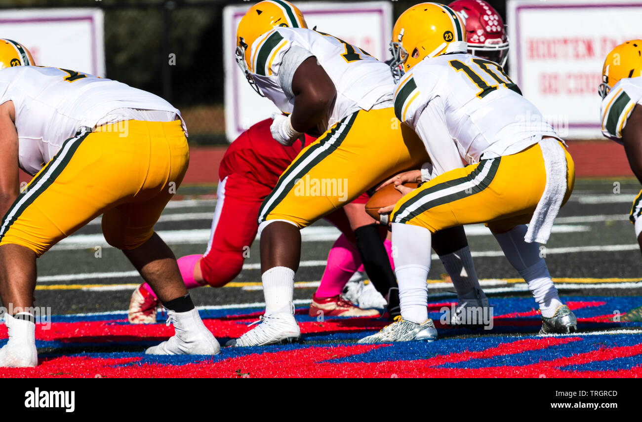 A high school quarter back is backing up after receiving the football from his center to start a play during a game. - Stock Image