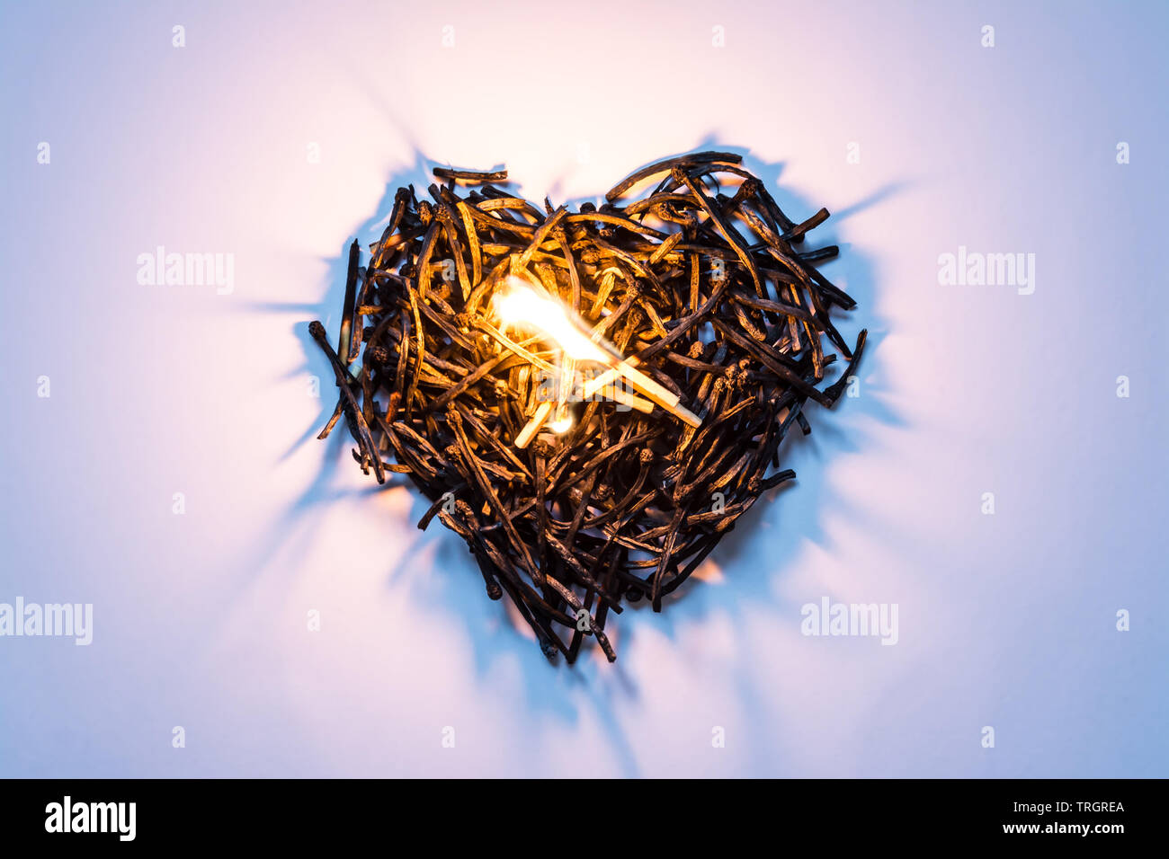 Heart symbol made of burned-down matches close-up with a burning match in the center and beautiful shadows. The concept of the complexity of love rela - Stock Image