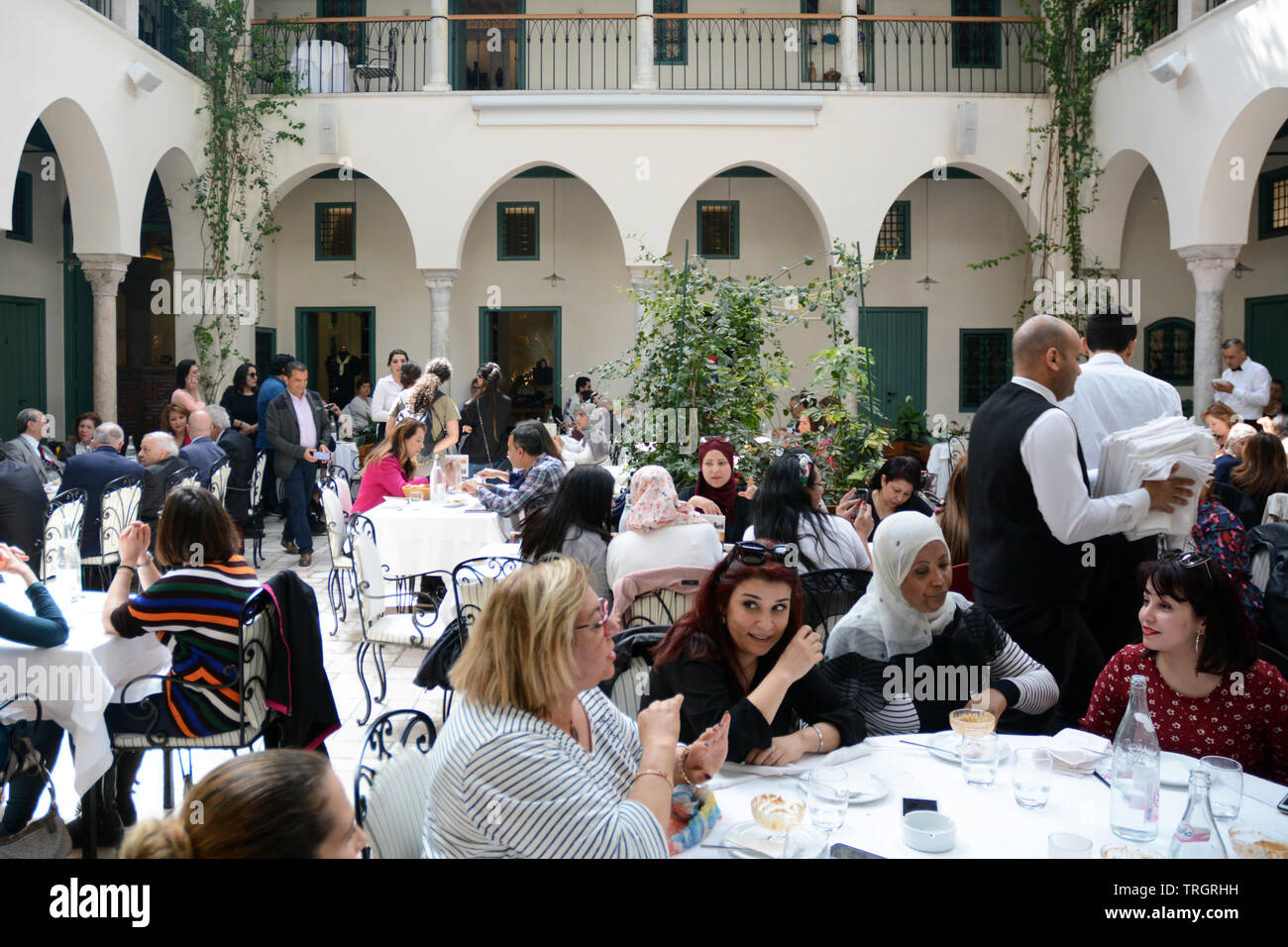 Tunisians having lunch at Fondouk El Attarine - a fine dining restaurant serving traditional Tunisian cuisine in the Medina of Tunis, Tunisia. Stock Photo