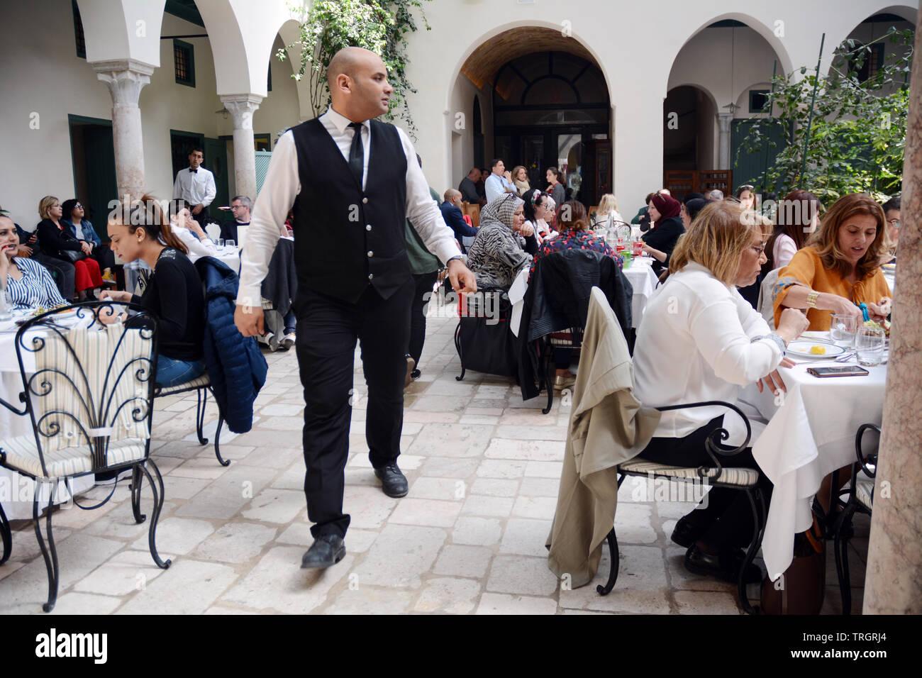 Tunisians having lunch at Fondouk El Attarine - a fine dining restaurant serving traditional Tunisian cuisine in the Medina of Tunis, Tunisia. Stock Photo