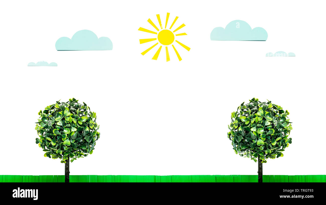 Paper sun, clouds, green grass and toy tree with green leaves isolated on white background. Funny summer landscape composition on the theme of good su - Stock Image