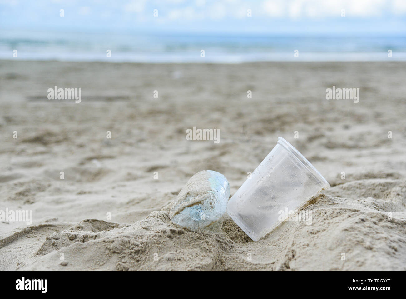 Garbage in the sea with plastic bottle , plastic cup and foam box on beach sandy dirty sea on the island / Environmental problem of rubbish pollution - Stock Image