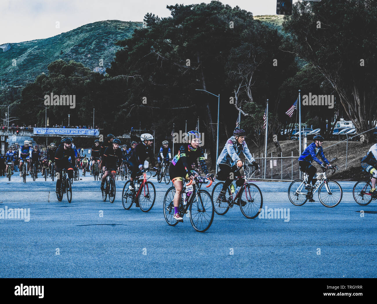 San Francisco, USA. 2nd June, 2019. Cyclists leave the Cow Palace at the start of the AIDS/Lifecycle just as the sun first reaches the hilltops above. Stock Photo