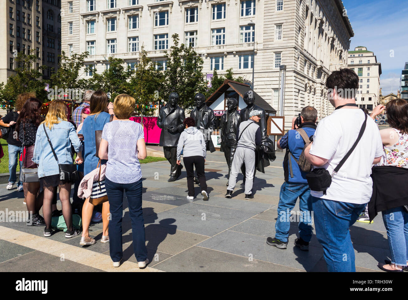 Tourists viewing the Beatles statue on Liverpool's Pier Head. The statue was unveiled in December 2015 and was a gift to the city by the Cavern Club. - Stock Image