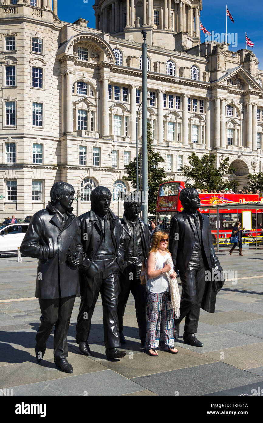 Woman posing for a photograph in front of the  Beatles statue on Liverpool's Pier Head. The statue was unveiled in December 2015. - Stock Image