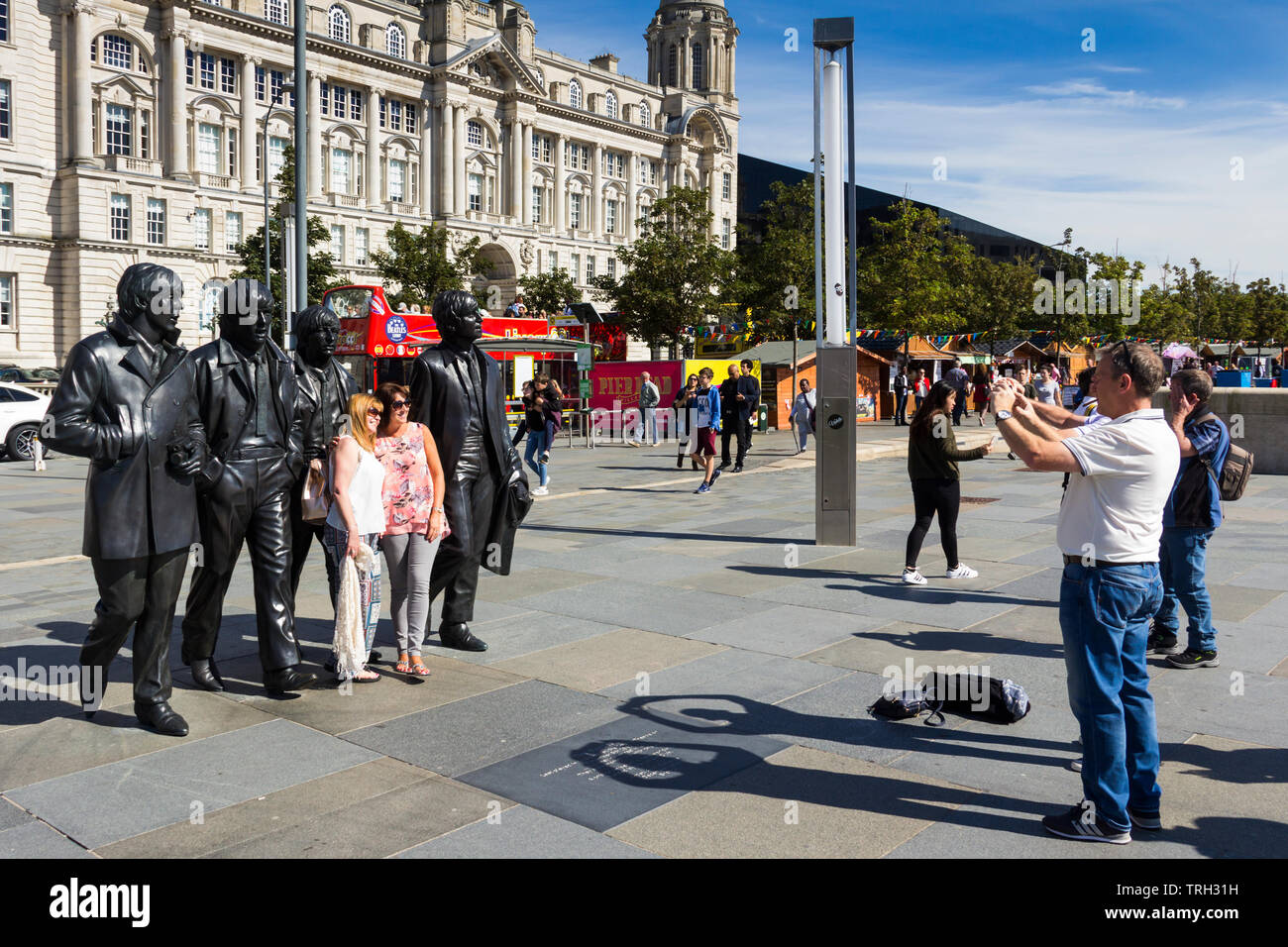 Two women posing for a photograph in front of the  Beatles statue on Liverpool's Pier Head. The statue was unveiled in December 2015. - Stock Image
