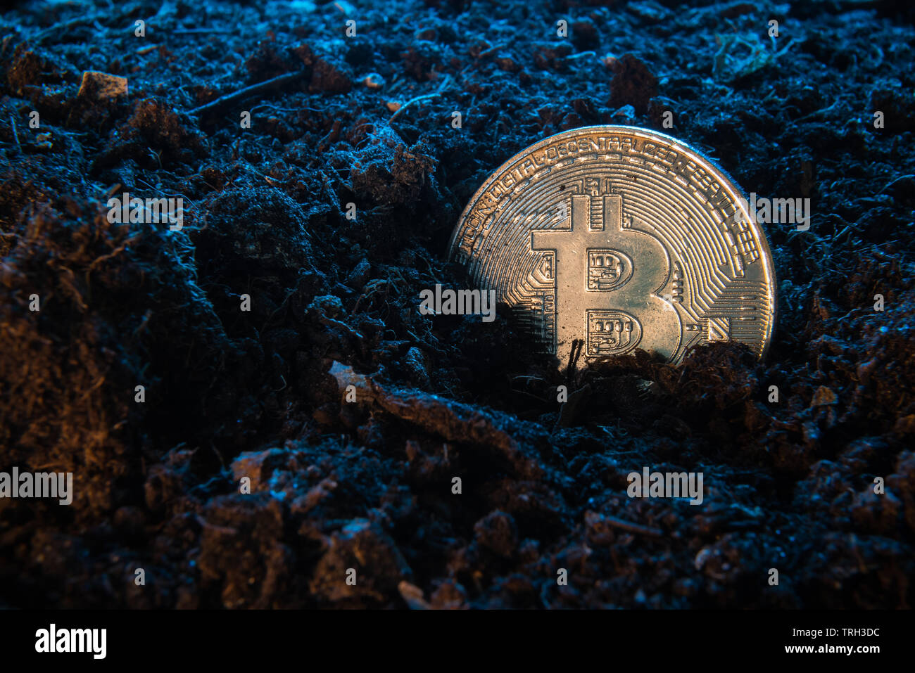 Mining crypto currency - Bitcoin. Online money coin in the dirt ground. Digital currency, block chain market, online business - Stock Image