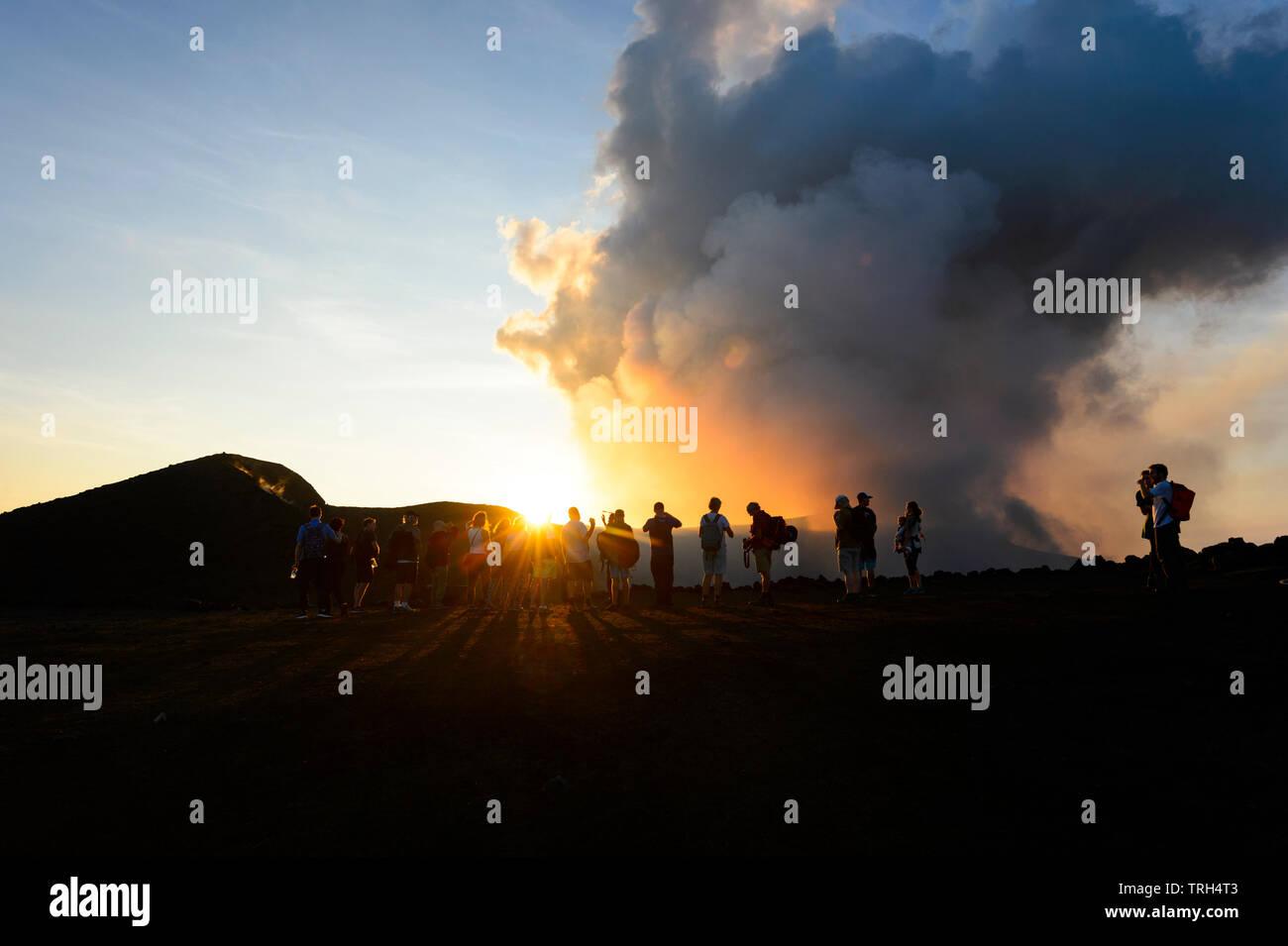 Tourists walking on the crater rim of smoking Mt Yasur Volcano at sunset, Tanna Island, Vanuatu - Stock Image