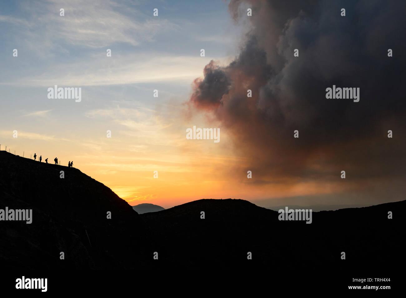 Silhouettes of tourists walking along the crater rim path, Mt Yasur Volcano at sunset, Tanna Island, Vanuatu - Stock Image