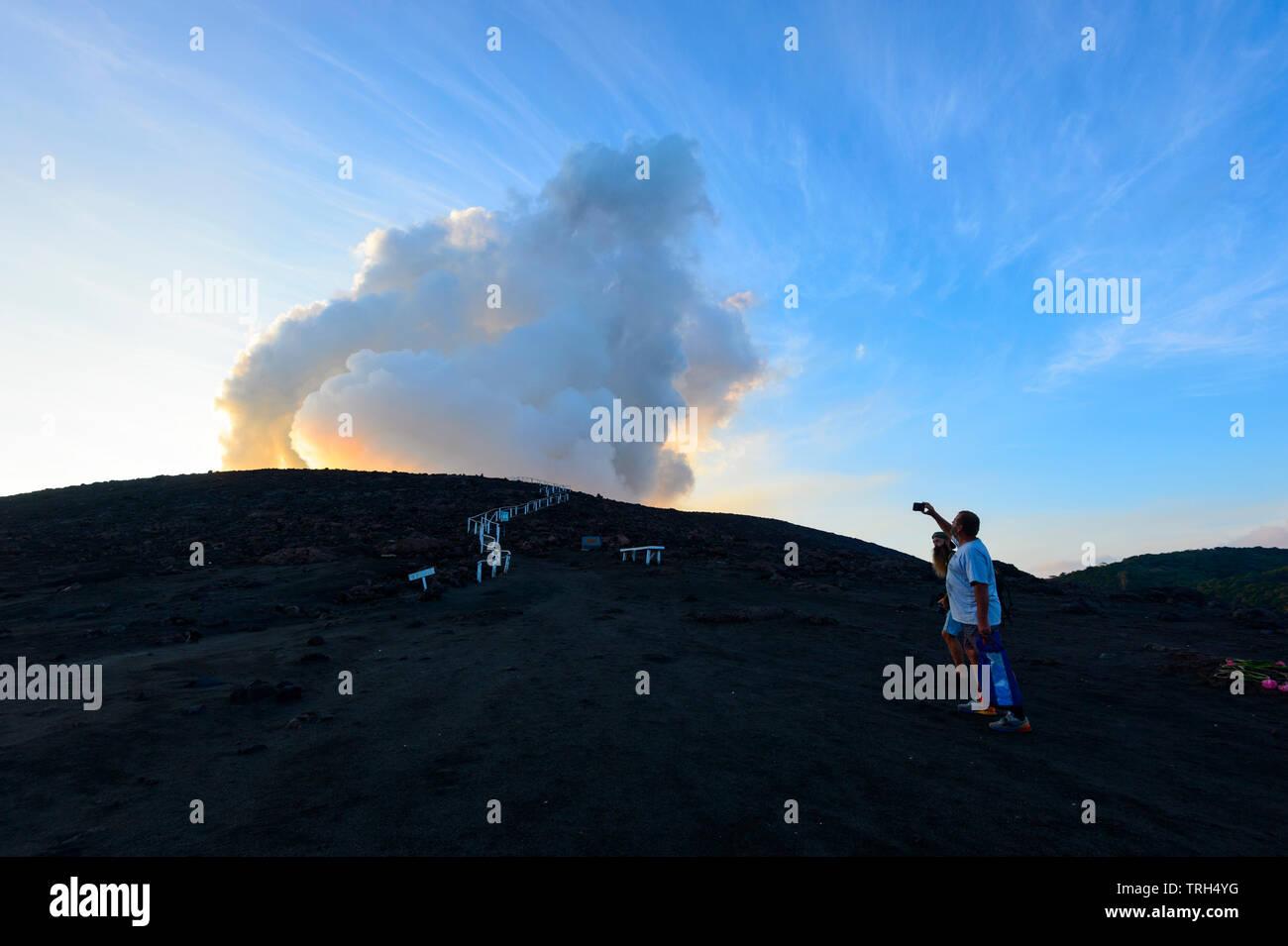 Tourists standing on the slopes of erupting Mt Yasur Volcano at sunset, Tanna Island, Vanuatu - Stock Image