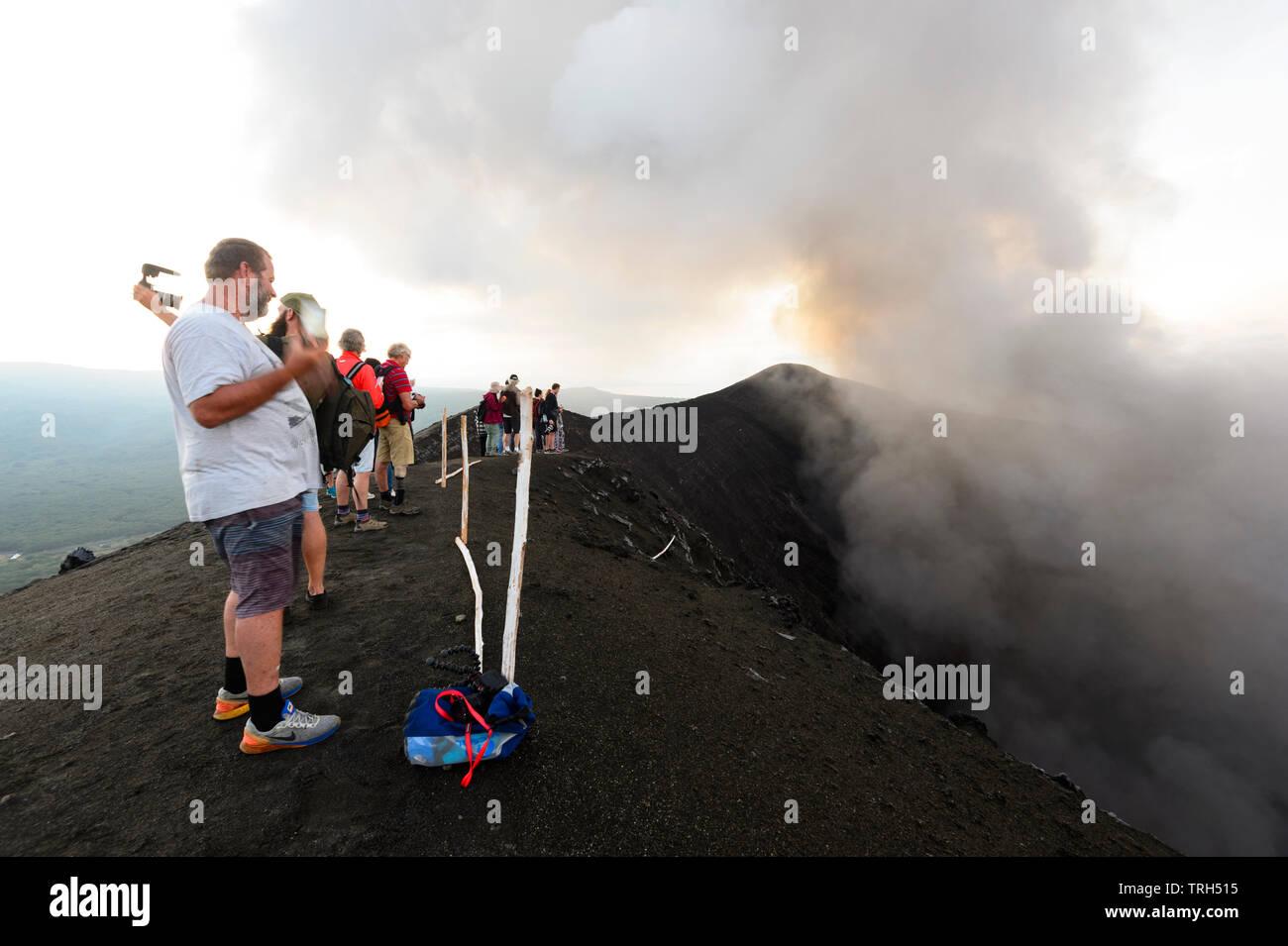 Tourists standing on the rim of erupting Mt Yasur Volcano at sunset, Tanna Island, Vanuatu - Stock Image