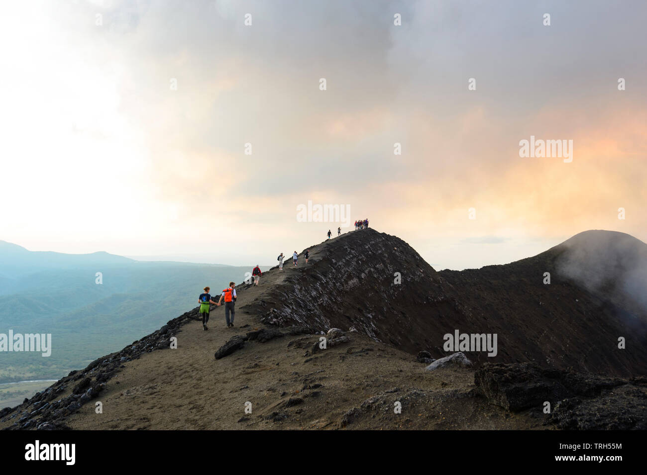 Tourists walking on the crater rim of Mt Yasur Volcano at sunset, Tanna Island, Vanuatu Stock Photo