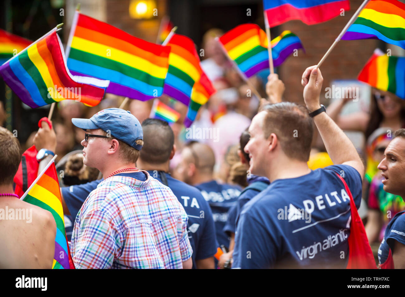 NEW YORK CITY - JUNE 25, 2017: Participants wearing shirts sponsored by Delta and Virgin Atlantic airlines wave rainbow flags in the gay Pride parade. - Stock Image