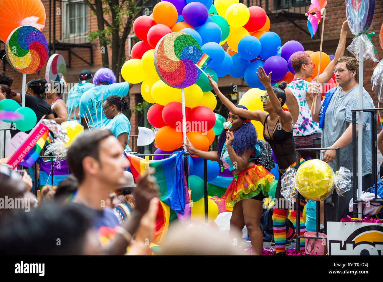 NEW YORK CITY - JUNE 25, 2017: Participants wave rainbow flags on a colorful float decorated with balloons in the annual Pride Parade in the Village. - Stock Image