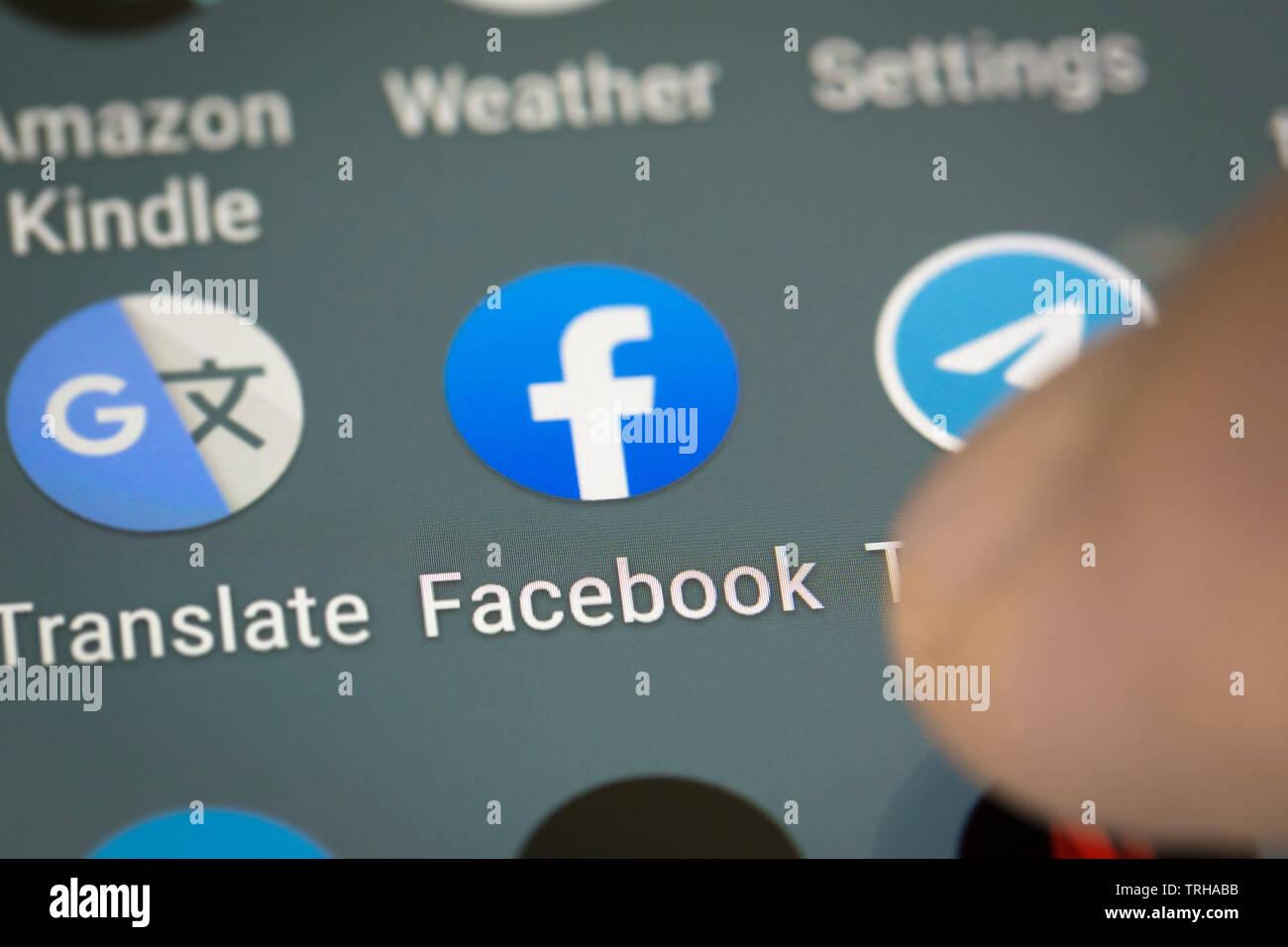 Facebook logo icon on mobile phone screen - Stock Image