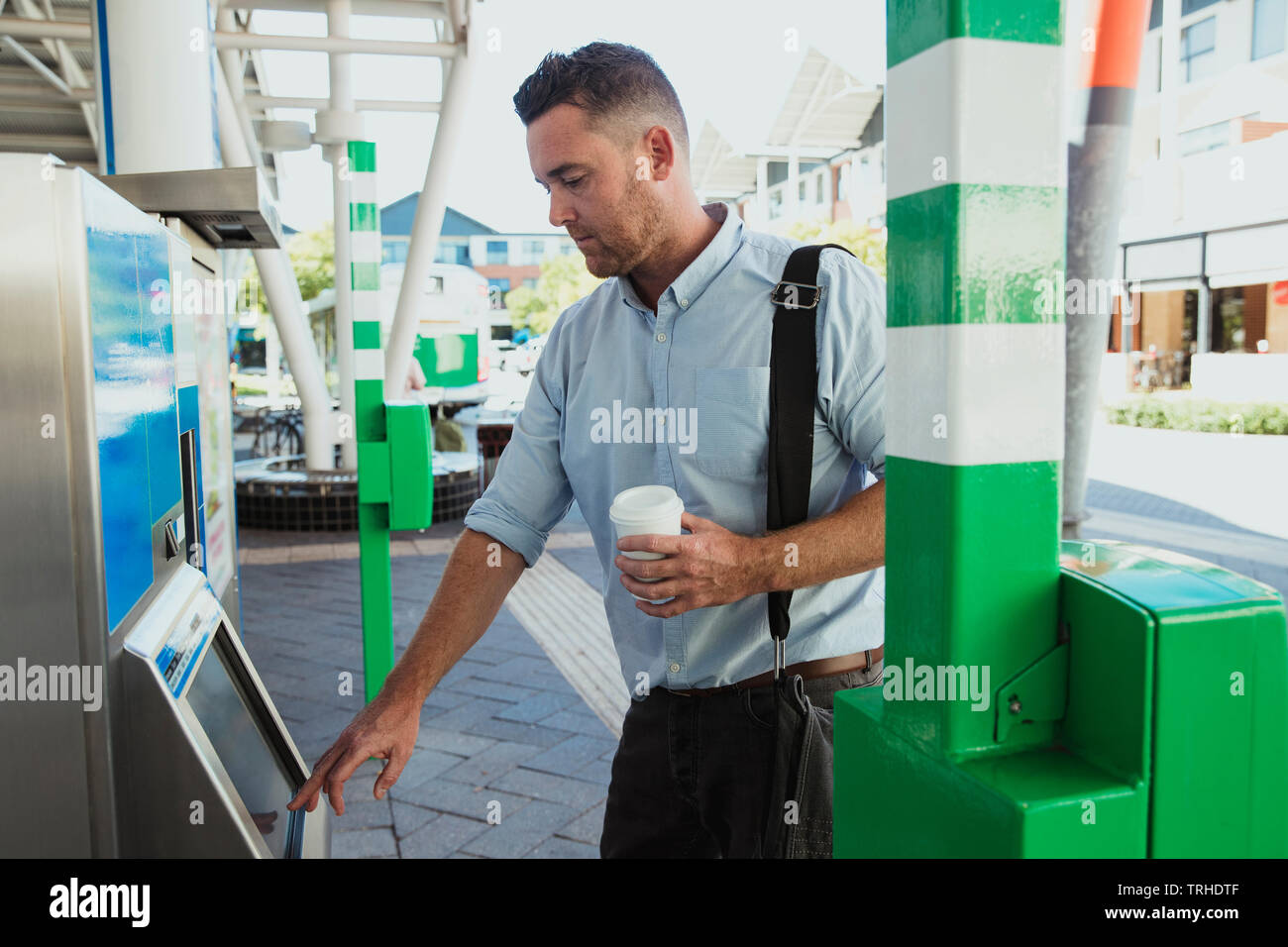 A side-view shot of a mid-adult businessman buying a train ticket to begin his commute to work, he is holding a cup of coffee. - Stock Image