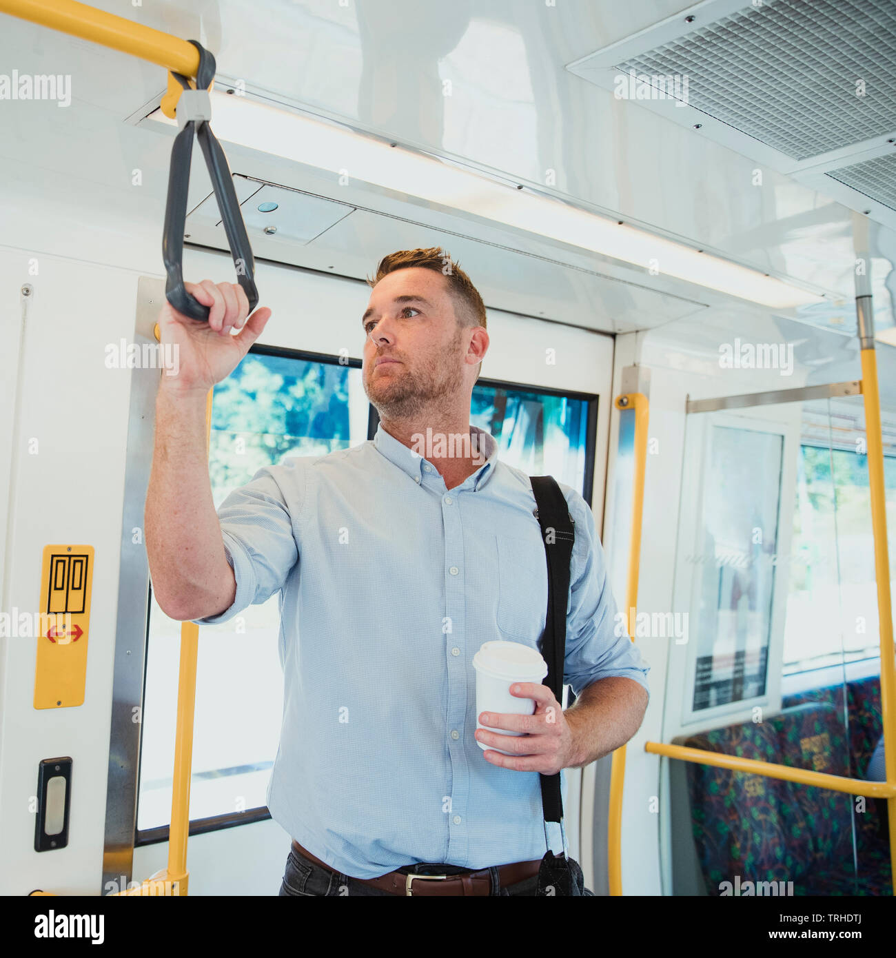 A side-view shot of a mid-adult businessman standing on a train commuting to work, he is holding a cup of coffee. - Stock Image