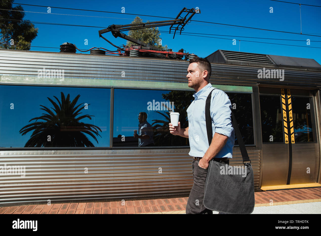A side-view shot of a mid-adult caucasian businessman walking down a railroad station platform with a cup of coffee in his hand, he is catching the tr - Stock Image