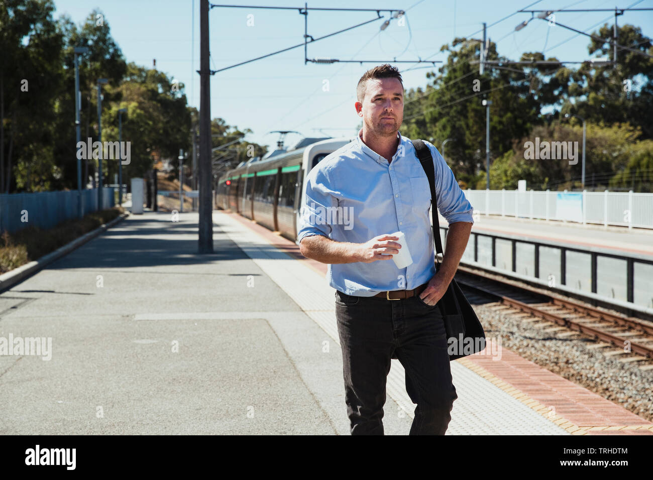 A front-view shot of a mid-adult caucasian businessman walking down a railroad station platform with a cup of coffee in his hand, he is catching the t - Stock Image