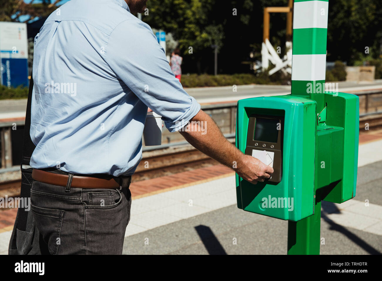 A rear-view shot of an unrecognizable mid-adult businessman buying a train ticket to begin his commute to work. - Stock Image