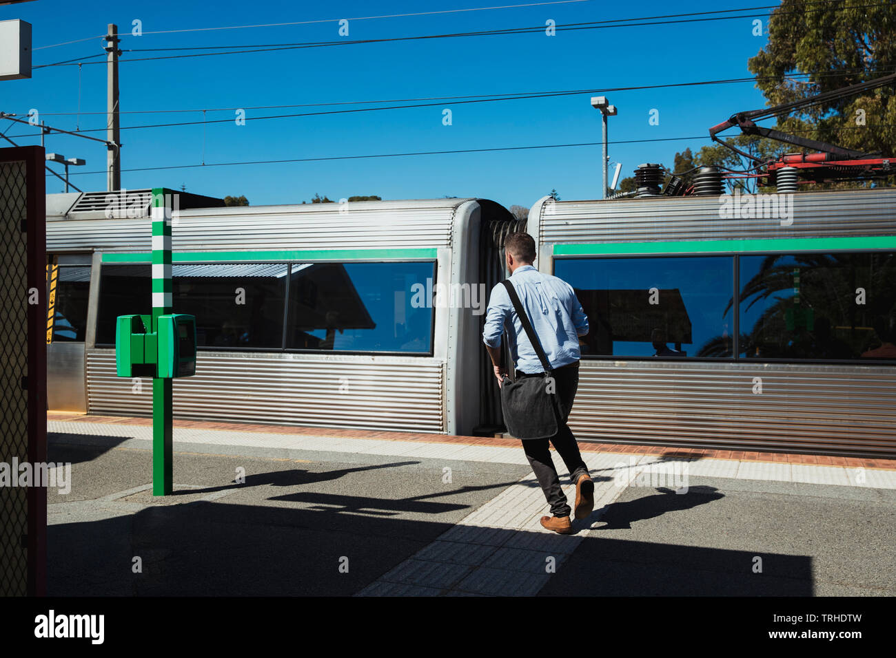 A rear-view shot of a mid-adult caucasian businessman running down a railroad station platform, he is trying to catch the train. - Stock Image