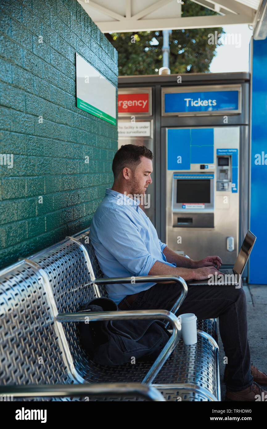 A side-view shot of a mid-adult caucasian businessman working on his laptop while he is sitting waiting for the train at a railroad station platform. - Stock Image