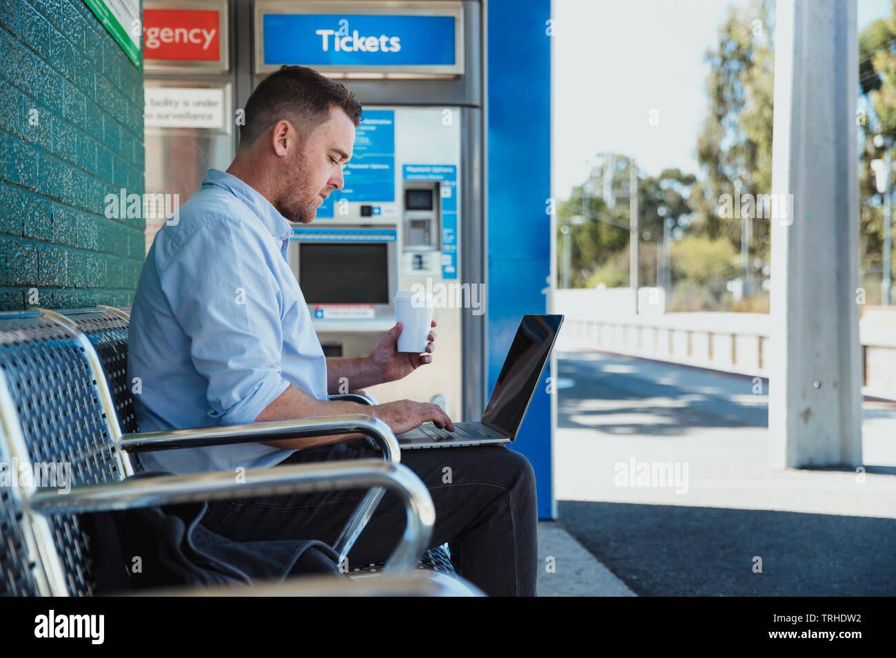 A side-view shot of a mid-adult caucasian businessman working on his laptop while he is sitting waiting for the train at a railroad station platform, - Stock Image